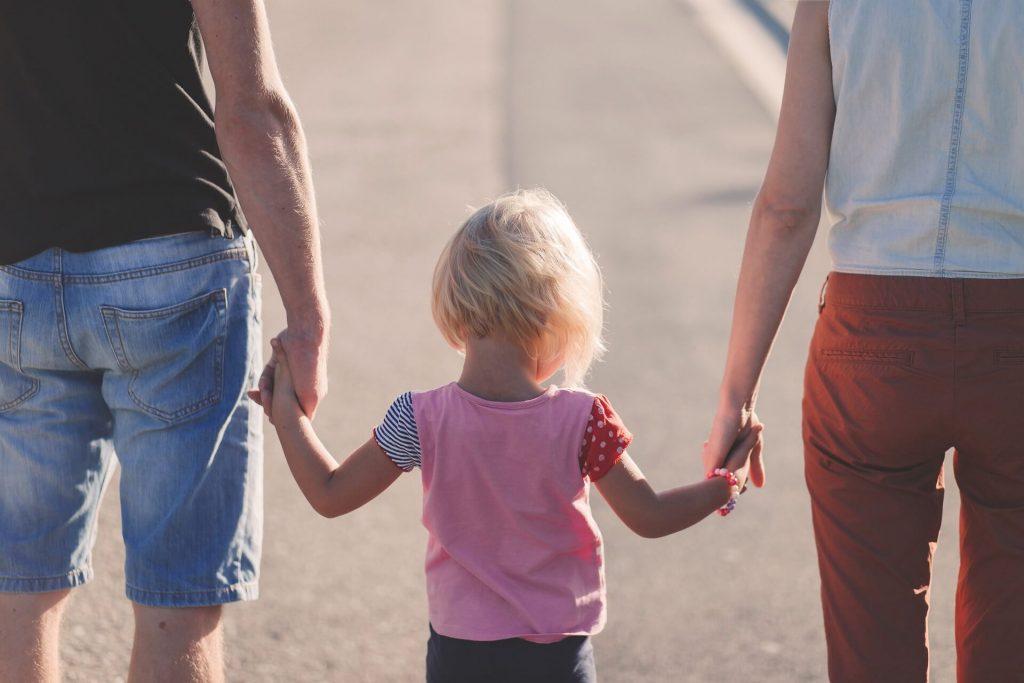 Παιδί που κρατά από το χέρι τους γονείς
